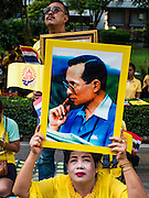 05 DECEMBER 2015 - BANGKOK, THAILAND:  A woman holds up a portrait of the King of Thailand in the plaza at Siriraj Hospital on the 88th birthday of Bhumibol Adulyadej, the King of Thailand. Hundreds of people crowded into the plaza hoping to catch a glimpse of the revered Monarch. The King has lived at Siriraj Hospital off and on for more than four years.    PHOTO BY JACK KURTZ