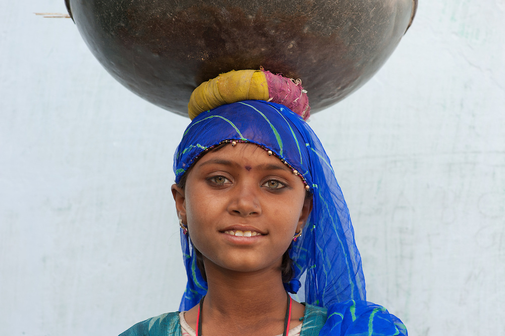 Young girl from the Indian Thar desert carrying dried cow dung used as fuel for cooking.