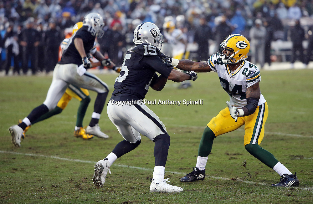 Green Bay Packers cornerback Quinten Rollins (24) bumps Oakland Raiders wide receiver Michael Crabtree (15) as he goes out for a pass during the 2015 week 15 regular season NFL football game against the Oakland Raiders on Sunday, Dec. 20, 2015 in Oakland, Calif. The Packers won the game 30-20. (©Paul Anthony Spinelli)