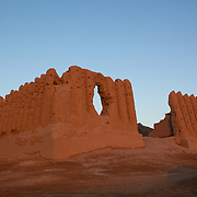 Early morning light shines golden red on Greater Kyz Kala, one of Merv's best preserved and most recognisable buildings. Merv is the site of several ancient cities founded over the millennia, now a UNESCO World Heritage Site archaeology park in Turkmenistan.  It is the country's biggest tourist destination, as Merv was a major silk road city in its day, and according to some British archaeologists, it was the world's biggest city in the mid 12th century (and was at least the 3rd largest).  It was one of the Islamic world's greatest centres of learning, with 12 libraries and countless books.  It also appears to have been the furthest west point that Buddhism ever reached, with the discovery of a Buddha head statue in a complex within one of the older city walls -- quite possibly a meditation complex or monastery. The city may have been home to up to 1 million people when it was sacked by the Mongols.  The city surrendered, but the invaders killed all its inhabitants, and despite the attempt to revive it during Timur's empire, the city never flourished again.  Now a modern soviet town, Mary, is nearby.