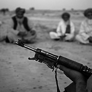 An Afghan police officer grips his AK-47 assault rifle, as village elders from Adamzai and Khenjakak comfront his unit and Canadian soldiers to release three men detained for being suspected insurgents in Panjwai District, Kandahar Province, Afghanistan.
