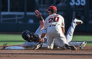 Infielder Carson Shaddy #20 of the Arkansas Razorbacks tags out Outfielder Kyle Nobach #28 of the Oregon State Beavers attempting to steal second base the second inning during game two of the College World Series Championship Series at TD Ameritrade Park in Omaha, Nebraska.