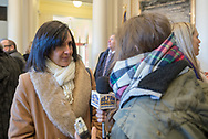 Mineola, New York, USA. January 1, 2018. Hemptead Town Clerk SYLVIA CABANA, a Democrat, is interviewed by a reporter for Hofstra University's WRHU radio station, after historic swearing-In of Laura Curran as Nassau County Executive. They were in the Theodore Roosevelt Executive & Legislative Building, which the Curran swearing-in was held in front of the entrance outdoors. Cabana's swearing in was held that morning at Hofstra University.
