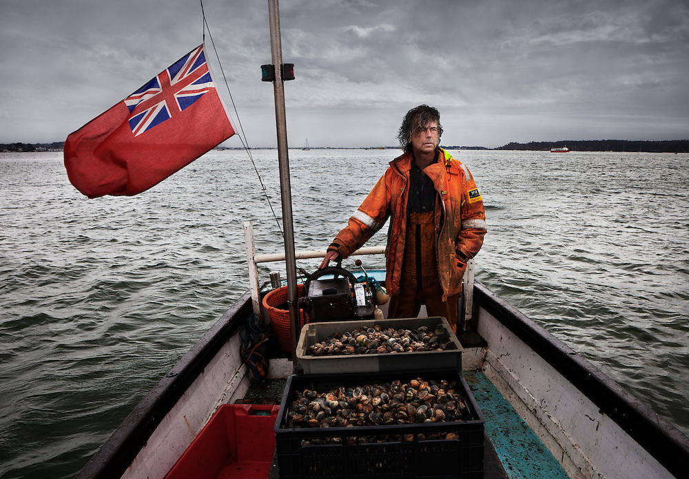 Pete Miles, fisherman, chef and owner of Storm Fish Restaurant and Dorset Oysters in Poole, aboard his boat &lsquo;Esperance&rsquo; in Poole Harbour, U.K.<br /> <br /> The flag is flying at half mast out of respect for Bill Hayes, a well known local fisherman and lifeboatman, who had died recently aged 92. <br /> <br /> Bill was from an old fishing family in Poole and it was him who taught Pete how to fish and handle a boat, while fishing together for many years.