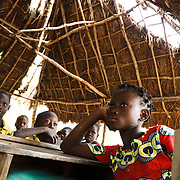 Children attend class under a thatched roof that was partially destroyed by heavy rains during floods in the village of Kpoto, Benin on Wednesday October 27, 2010.