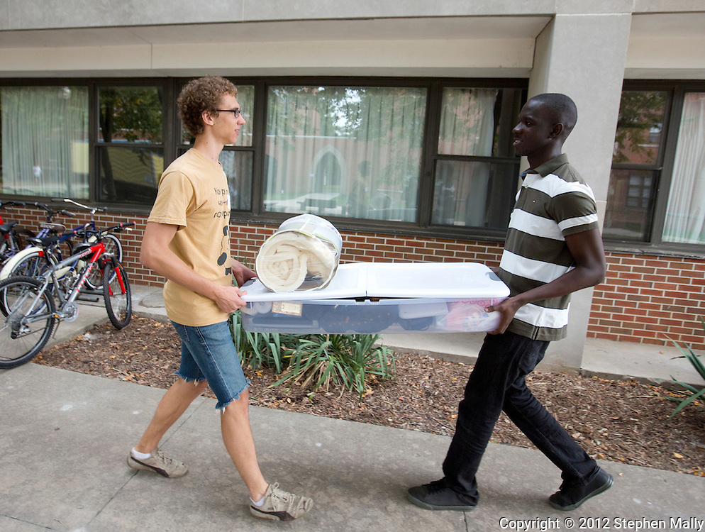 Karl Sadkowski (from left), 18, of Cedar Falls, Iowa talks with his roommate, Reggie Sackey-Addo, 17, of Accra, Ghana as they carry a load of his belongings to their room at Grinnell College in Grinnell, Iowa on Saturday, August 25, 2012.