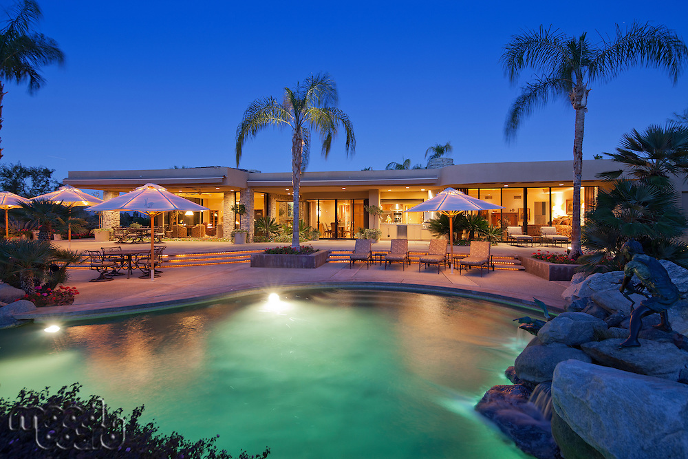 view across a pool to patio of luxury home