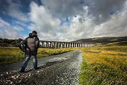 © Licensed to London News Pictures. 26/08/2015. Ribblehead, UK. After a gloomy start the cloud cover has broken to light up the Ribbleshead Viaduct in the Yorkshire Dales. Photo credit: Andrew McCaren/LNP