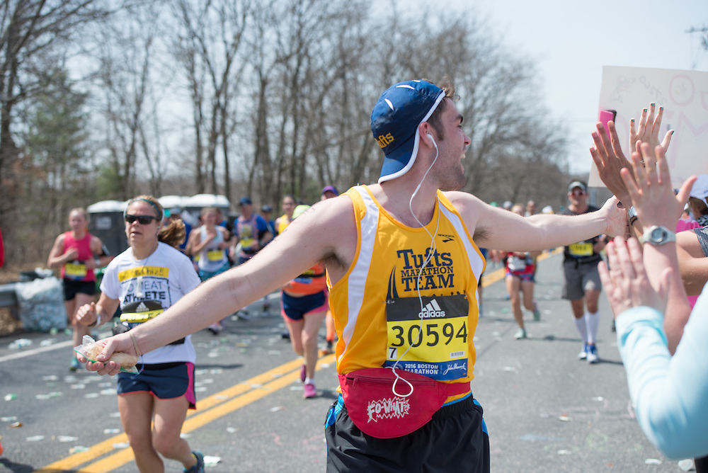 4/18/16 – Natick, MA – Colin Burnett (LA'16) runs past cheering friends at Mile 9 of the 2016 Boston Marathon in Natick, MA on April. 18, 2016. (Sofie Hecht / The Tufts Daily)