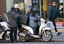 © Licensed to London News Pictures. 01/04/2020. London, UK. Food delivery drivers ignore social distancing rules in Kensington High Street. Death rates from the spread of coronavirus continue to climb. Photo credit: LNP