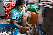 02 MARCH 2014 - MYAWADDY, KAYIN, MYANMAR (BURMA):  A worker peels garlic in a warehouse in Myawaddy, Myanmar. Myawaddy is separated from the Thai border town of Mae Sot by the Moei River. Myawaddy is the most important trading point between Myanmar (Burma) and Thailand.     PHOTO BY JACK KURTZ