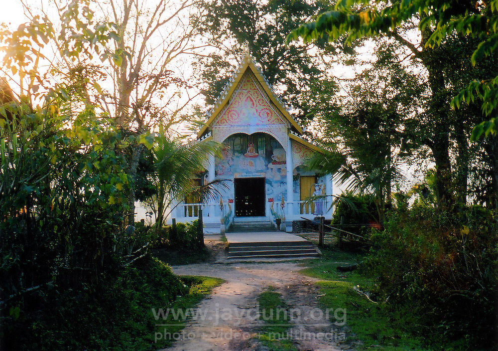 "Laos, Luang Nam Tha, 2003. Though this tiny Buddhist temple, or ""wat,"" is far from town, it is home to two young brothers, who maintain it with care."