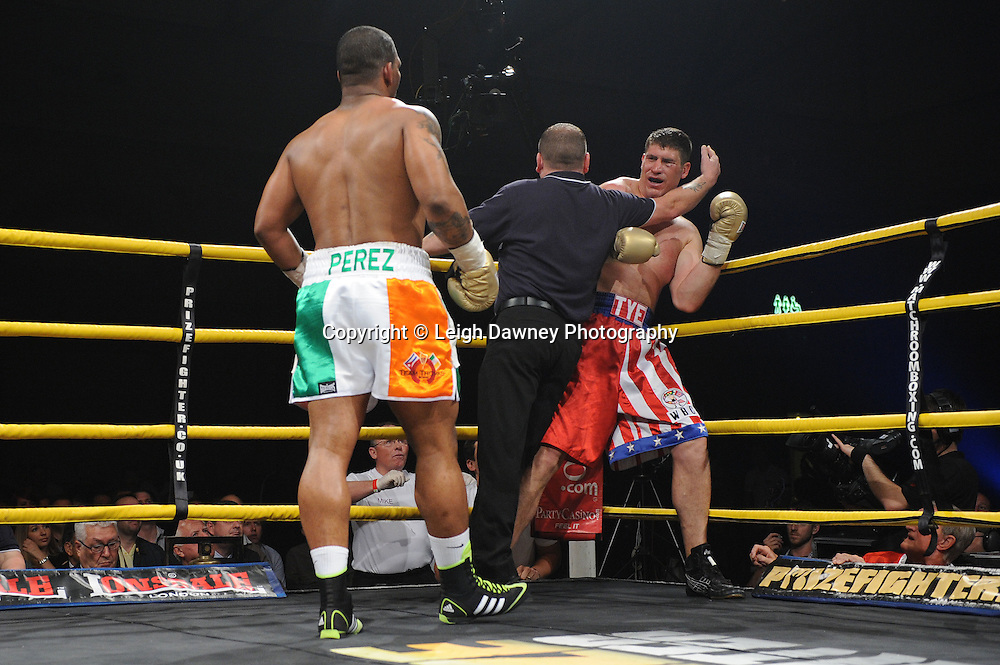 Referee stops the fight after Mike Perez (Irish colour shorts) punishes Tye Fields in the corner to claim the title of Prizefighter International on Saturday 7th May 2011. Prizefighter / Matchroom. Photo credit © Leigh Dawney. Alexandra Palace, London.