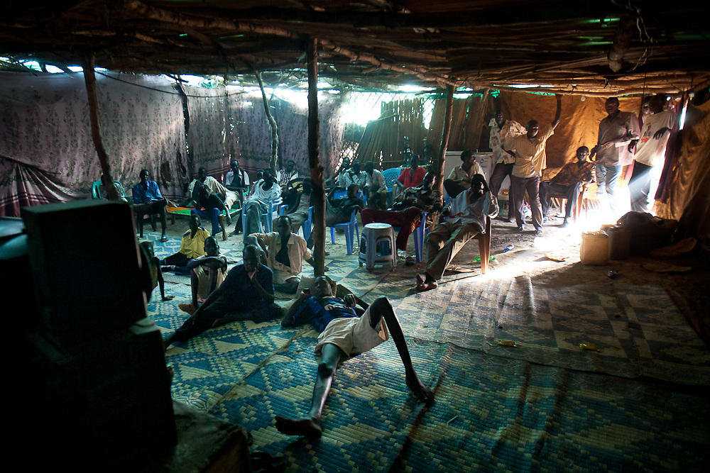 Youth watch action movies in a grass reed hall in Bentiu on April 29, 2010. Education and employment are hard to get in South Sudan living few opportuntities for the youth. Many find themselves involved in local militias as it is the only way to advance.
