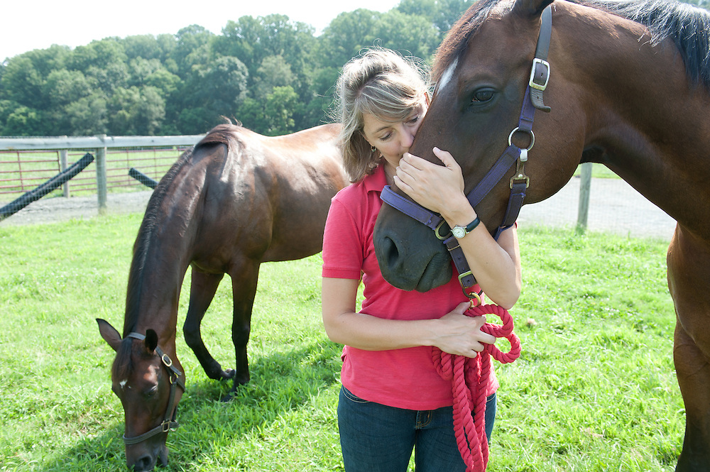 Female equestrian instructor and rider giving a kiss and hugging a horse in front of horse stables