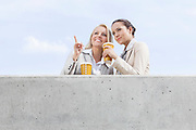 Low angle view of young businesswomen with disposable coffee cups looking away while standing on terrace against sky
