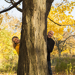 A young couple, peeking out from behind a tree