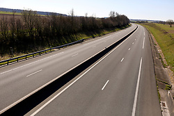 23 March 2020. Near Montreuil Sur Mer, Pas de Calais, France. <br /> Coronavirus - COVID-19 in Northern France.<br /> <br /> The usually busy A16 toll motorway from Calais to Paris is deserted. The A16 is one of France's main arteries carrying freight, tourists and people North and South from the Belgian border servicing Dunkirk, Calais, Boulogne, Dieppe, and Havre with connections to Paris and the french interior. <br /> <br /> From March 16th French lawmakers imposed strict controls on the movement of people in an effort to stem the spread of the virus. Anyone leaving their home must carry with them an 'attestation,' in a effect a self administered permit to allow them out of the house. If stopped by the police, one must produce a valid permit along with identification papers. Failure to do so is punishable with heavy fines. Movement in France has been heavily restricted by the government.<br /> <br /> Montreuil Sur Mer was the headquarters of the British Army under Field-Marshal Sir Douglas Haig from March 1916 to April 1919. Over 1,200 year old, the ancient fortified  town with its high ramparts has endured through history, surviving the plague and King Henry VIII's invasion of France in 1544 when the Duke of Norfolk under Henry VIII's command laid a disastrous siege to the town which held firm until Norfolk was forced to withdraw in 1545. Residents are confident the ancient town can survive the coronavirus too. <br /> Photo©; Charlie Varley/varleypix.com