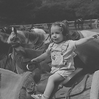 1. When was this photo taken?<br /> <br /> 1992<br /> <br /> 2. Where was this photo taken?<br /> <br /> Upstate New York at a Dude Ranch<br /> <br /> 3. Who took this photo?<br /> <br /> Nancy Kaye<br /> <br /> 4. What are we looking at here? <br /> <br /> My daughter Dana, then a toddler, on a horse at a family reunion at a dude ranch in upstate New York.<br /> <br /> 5. How does this old photo make you feel?<br /> <br /> I am surprised at how much my daughter, even at this young age, displayed the personality that we see in her now as a 27-year-old. She is someone who knows her own mind and is always ready to participate in new experiences. At the time I took the photo, this trait seemed like stubbornness and was a challenge to me as a new mom. Seeing the image makes me feel the pointed and poignant passage of time. It makes me wish I could re-experience that period in my life.<br /> <br /> 6. Is this what you expected to see?<br /> <br /> No, I had forgotten about these images and the details of this extended family reunion.<br /> <br /> 7. Does this photo bring back any memories?<br /> <br /> Yes. It brings back the time in my life when parenting was new, as well as restore the memories of a joyous time with members of my family.<br /> <br /> 8. How do you think others will respond to this photo? <br /> <br /> I think some people will be struck by the poise of this confident little girl by herself on a big horse. And perhaps it will evoke similar feelings of poignancy among others whose children are now young adults, but whose childhood seems like just a moment ago.