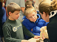 Boone Asher (from left), 9, and Wyatt Asher, 10, both of Van Horne talk with Coe Pre-Nursing student Tracey Allen of Tipton about a skull in the Rattling Bones room at the 11th annual Coe College Playground of Science at Peterson Hall of Science in Cedar Rapids on Thursday, October 24, 2013. Faculty and students from the physics, biology, chemistry, mathematics, computer science, nursing, psychology and ROTC departments provided demonstrations and facilitated hands-on opportunities to show students of all ages that science can be fun.