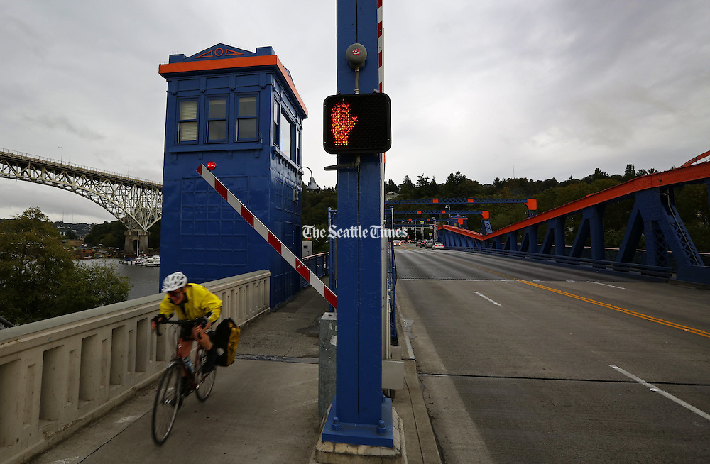 Seattle's bridges are more than just connectors, we interact with them, like this cyclist peddling fast northbound over the Fremont Bridge.<br />