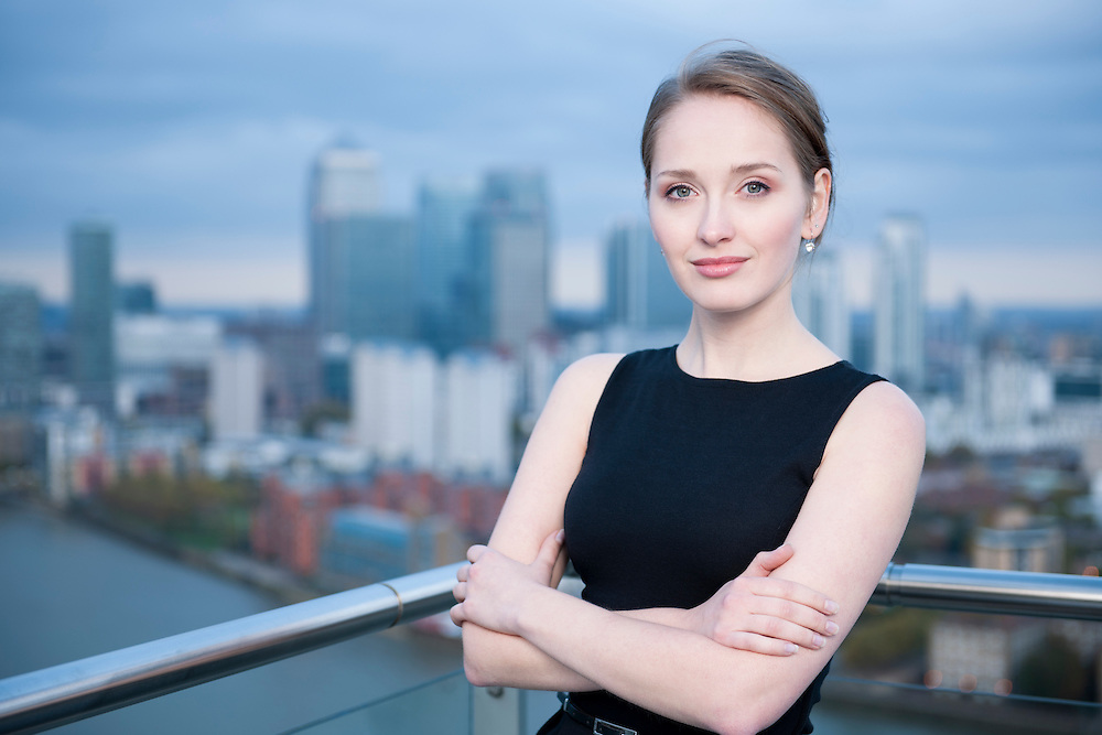 Attractive young redhead businesswoman with skyscrapers of a modern city in the background<br /> Buy here -<br /> http://www.istockphoto.com/stock-photo-18328129-city-businesswoman.php?st=71a5945