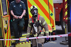 © Licensed to London News Pictures. 01/04/2020. London, UK. LFB (London Fire Brigade) using full facerespirators normally reserved for firefighting at an incident involving all emergency services a suspected COVID-19 case is isolatedand removed from home. Uxbridge Road in Shepherd's Bush was closed for an hour as ambulance, fire brigade and police attended, extracting the patient by crane from a three story apartment building in West London. PPE (personal protective equipment) was in evidence, with the fire brigade. Ambulance workers decontaminated the scene and reusable equipment before moving on.  Photo credit: Guilhem Baker/LNP
