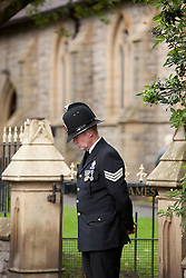 © Licensed to London News Pictures. 19/07/2012. Oldham , UK . The funeral of 2 year old Jamie Heaton , who was killed in a blast in his home on 26/06/2012 . A policeman guards the gate prior to the funeral . He bows his head in respect for mourners . Photo credit : Joel Goodman/LNP