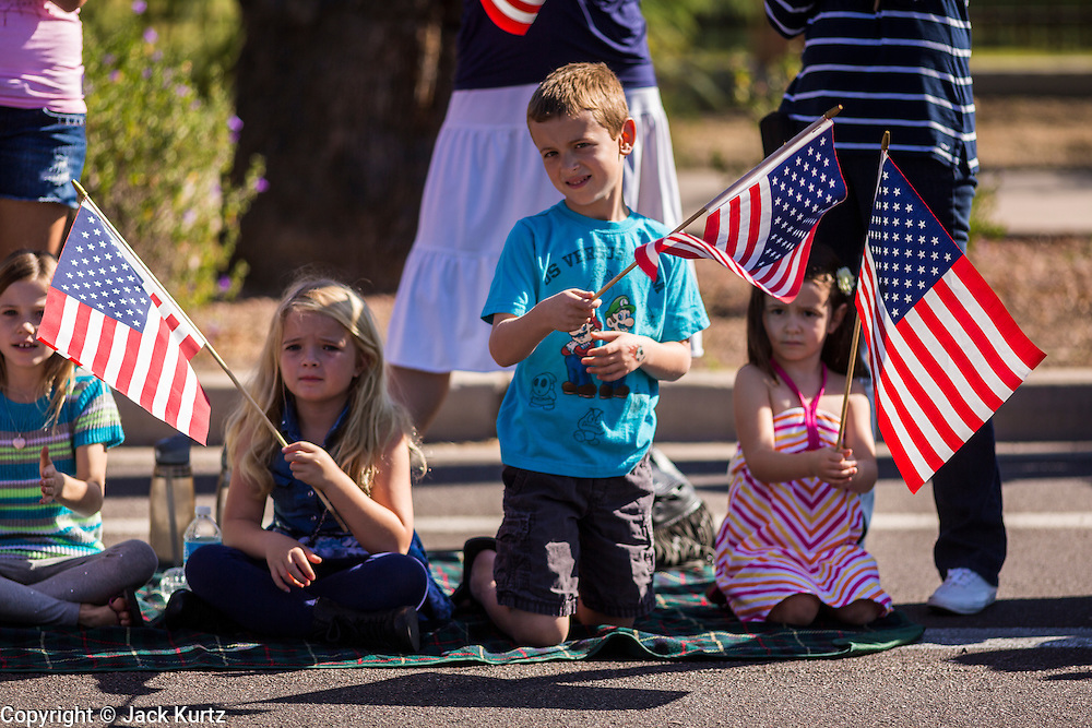 "11 NOVEMBER 2013 - PHOENIX, AZ: Spectators cheer passing veterans at the Phoenix Veterans Day Parade. The Phoenix Veterans Day Parade is one of the largest in the United States. Thousands of people line the 3.5 mile parade route and more than 85 units participate in the parade. The theme of this year's parade is ""saluting America's veterans.""     PHOTO BY JACK KURTZ"