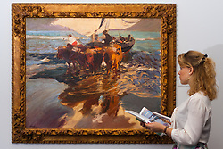 Sotheby's, London, December 5th 2014. World renowned aution house Sotheby's is to offer a collection of British and Continental masters to be sold at auction on December 10th 2014. PICTURED: A woman admires the bold brushstrokes of Joaquin Sorolla's Vuelta de la Pesca, Playa Valencia (The return from fishing, Valencia beach) which is expected to fetch between £1,4 and 1.8million at auction.
