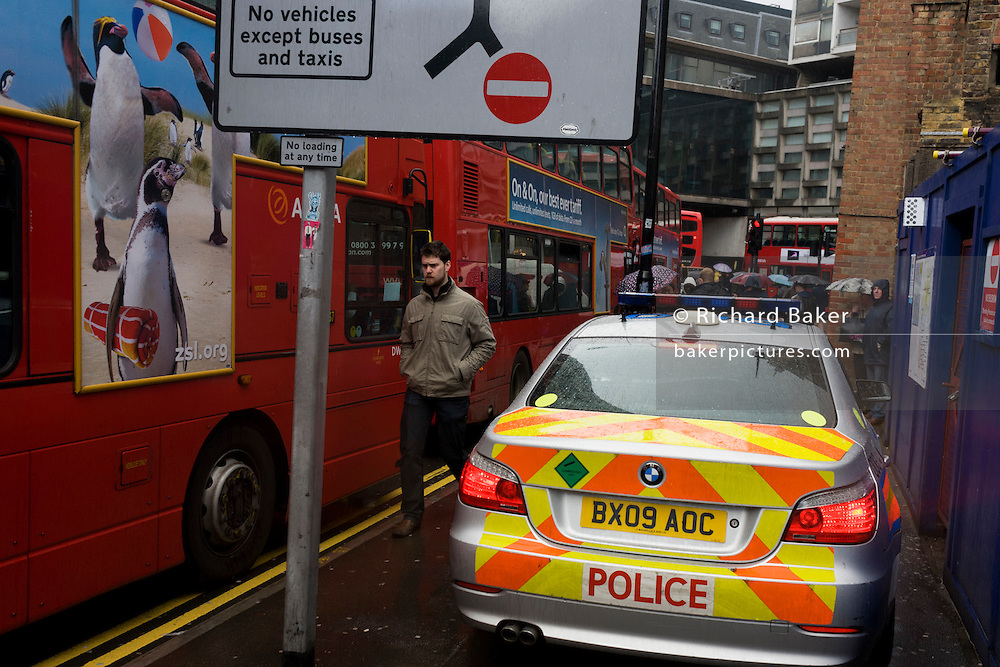 A Metropolitan police car drives carefully past pedestrians and stationary traffic during a central London emergency.
