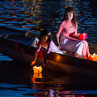 HOI AN , VIETNAM - OCT 04 : Vietnamese mother and daughter dropping lanterns into the river in Hoi An Vietnam during the Hoi An Full Moon Lantern Festival on October 04 2017