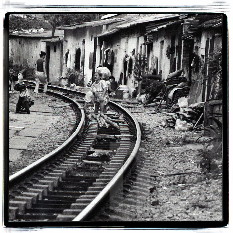 A Vietnamese woman sits on a plastic chair in the middle of the railway, Hanoi, Vietnam, Southeast Asia. Locals go about their business along the tracks between train crossings.