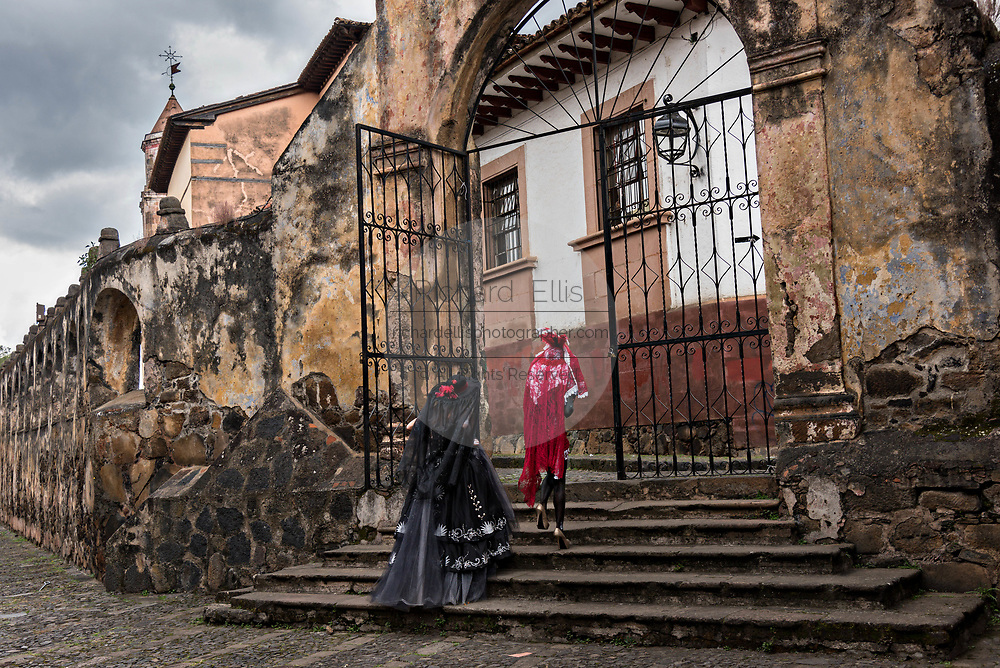 Young Mexican women dressed in La Calavera Catrina costumes walk through the courtyard of the Templo del Sagrario during the Day of the Dead or Día de Muertos festival October 31, 2017 in Patzcuaro, Michoacan, Mexico. The festival has been celebrated since the Aztec empire celebrates ancestors and deceased loved ones.