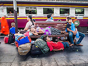 11 APRIL 2015 - BANGKOK, THAILAND:  People sleep while they wait to board a train at Hua Lamphong train station in Bangkok. More than 130,000 passengers streamed through Bangkok's main train station Friday ahead of Songkran, Thailand's traditional new year celebration. Songkran will be celebrated April 13-15 but people started streaming out of Bangkok on April 10 to go back to their home provinces.   PHOTO BY JACK KURTZ