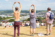 The sun continues to shine on the second day of Glastonbury Festival after it opened it's gates yesterday for the early arrivals. Approximately 170,000 revellers are set to turn up to the festival which is hosting a number of headliners including Kanye West and Alt J. <br /> Pictured: A festival goer (centre) enjoys a free yoga lesson overlooking the festival ground.