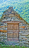 Old wooden door in a pyramid shaped stone building in Ticino, Switzerland.  The setting and the forested background lends this photo a luminous, surreal quality.