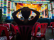 "18 AUGUST 2014 - BANGKOK, THAILAND:      A member of the audience relaxes while she watches the Lehigh Leng Kaitoung Opera troupe perform during a performance at Chaomae Thapthim Shrine, a small Chinese shrine in a working class neighborhood of Bangkok. The performance was for Ghost Month. Chinese opera was once very popular in Thailand, where it is called ""Ngiew."" It is usually performed in the Teochew language. Millions of Chinese emigrated to Thailand (then Siam) in the 18th and 19th centuries and brought their culture with them. Recently the popularity of ngiew has faded as people turn to performances of opera on DVD or movies. There are still as many 30 Chinese opera troupes left in Bangkok and its environs. They are especially busy during Chinese New Year and Chinese holiday when they travel from Chinese temple to Chinese temple performing on stages they put up in streets near the temple, sometimes sleeping on hammocks they sling under their stage. Most of the Chinese operas from Bangkok travel to Malaysia for Ghost Month, leaving just a few to perform in Bangkok.   PHOTO BY JACK KURTZ"