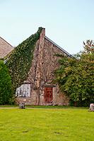 Vine covered stone building near Chateau  de Commarin, France.