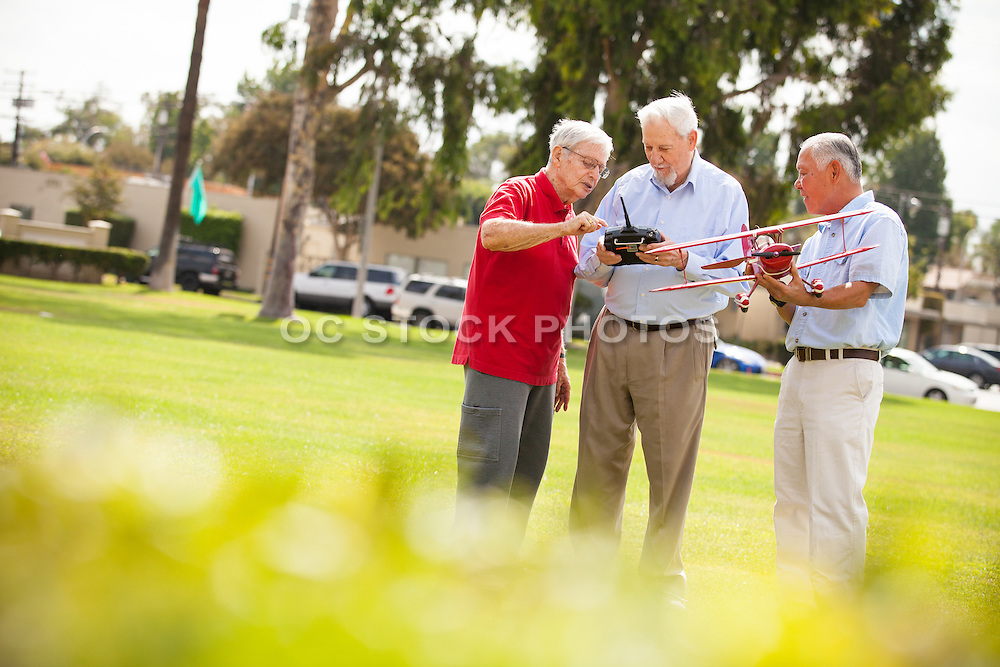 Senior Friends Enjoying a Remote Control Model Airplane at the Park