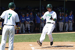 11 April 2015:  Jarrod Juskiewicz hustles home on a hit by Gino Cavalieri and gets greeted by Nick Huskisson during an NCAA division 3 College Conference of Illinois and Wisconsin (CCIW) Pay in Baseball game during the Conference Championship series between the Millikin Big Blue and the Illinois Wesleyan Titans at Jack Horenberger Stadium, Bloomington IL
