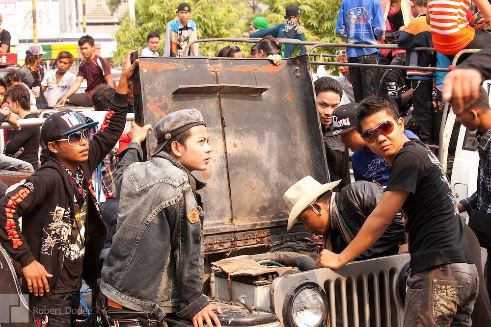 Mandalay, Myanmar- April 14, 2013: This is not a great time to have a breakdown, but these young men attempt a repair and make the best of it during Myanmar's Thingyan Water Festival. Thingyan is held in April, one of the hottest months of the year in Myanmar. The water festival marks the country's New Year celebration and the festival includes lots of drinking, singing, dancing and theater. Wherever you are you are likely to get doused with water as the Burmese see this as a cleansing of the previous year's sins and bad luck and a blessing for good luck and prosperity in the year ahead. In the major cities of Mandalay and Yangon, large platforms are erected along major roadways and are equipped with high powered water hoses. The platforms, sponsored by large corporate donors, also have dance stages and play the latest pop and hip hop music. Thousands of residents pour into the streets by foot, motorbike and flatbed truck to get hosed under the platforms while they drink and dance. Many of the young celebrants wear their best clubbing clothes. And many of the party goers are men, having left their wives and girlfriends at home.