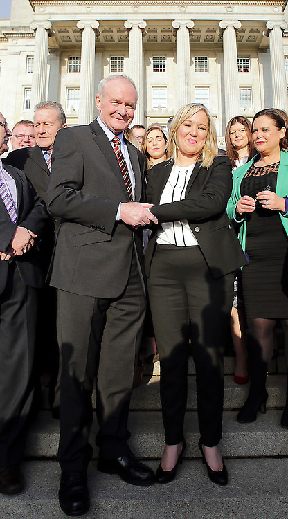 © Licensed to London News Pictures. STORMONT BELFAST - 23 JAN 2017: Sinn Fein's Michelle O'Neill (right) shakes hands with Martin McGuinness, on the steps of Stormont after being named as the new leader of Sinn Fein in the North, taking over from former deputy first minister Martin McGuinness who has retired due to illness. Photo credit: London News Pictures.