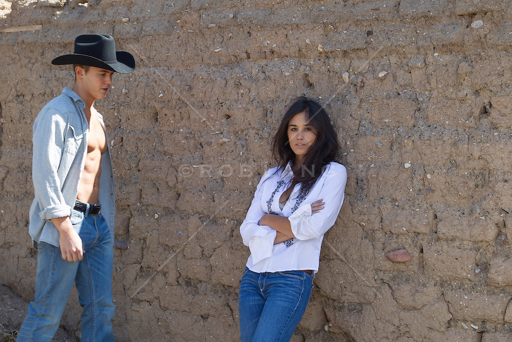 cowboy walking towards a beautiful girl leaning against an adobe wall in New Mexico