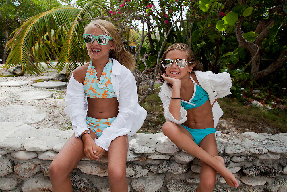 Portrait of two 10 year old caucasian girls wearing bikini's and sunglasses on summer holiday
