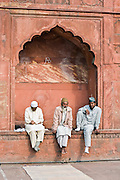 INDIA, OLD DELHI:  Three Muslim East Indian men sit together in an alcove in the courtyard of the Jama Masjid Mosque in Old Delhi as they wait for prayer time.