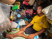 14 SEPTEMBER 2015 - BANGKOK, THAILAND:  A man listens to his portable radio in the tiny room he rents near Wat Kalayanamit. The room is about four feet by four feet, too small for him to layout in. He lives alone and is one of the renters being evicted from their homes near the temple. Fiftyfour homes around Wat Kalayanamit, a historic Buddhist temple on the Chao Phraya River in the Thonburi section of Bangkok are being razed and the residents evicted to make way for new development at the temple. The abbot of the temple said he was evicting the residents, who have lived on the temple grounds for generations, because their homes are unsafe and because he wants to improve the temple grounds. The evictions are a part of a Bangkok trend, especially along the Chao Phraya River and BTS light rail lines. Low income people are being evicted from their long time homes to make way for urban renewal.           PHOTO BY JACK KURTZ