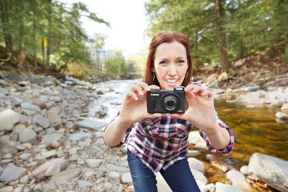 Lifestyle image of girl with small camera by river in Catskills Upstate New York