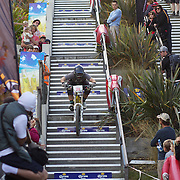 James Hampton from Christchurch tackles the Brecon Street steps in Queenstown during the Corona Dirtmasters Downhill event in Queenstown, Central Otago. Eighty competitors tackled the technically demanding course which started at the Gondola summit and finishied with a run down the steps in Brecon Street, Queenstown. The event was part of the inaugural Queenstown Bike Festival, which took place from 16th-25th April. The event hopes to highlight Queenstown's growing profile as one of the three leading biking centres in the world. Queenstown, Central Otago, New Zealand. 24th April 2011. Photo Tim Clayton..