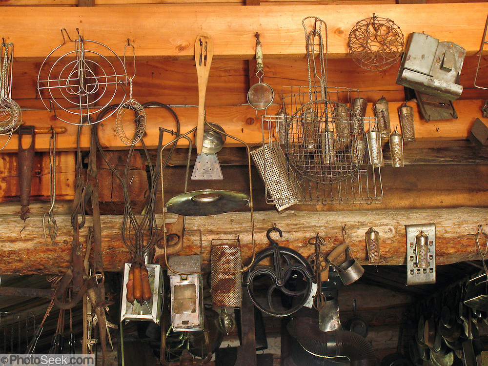 """Kitchen gadgets hang in the late 1800s restored Frontier Ladies Dry Goods Store in Nevada City, Montana, USA. Nevada City was a booming placer gold mining camp from 1863-1876, but quickly declined into a virtual ghost town. This fascinating town inspires you to imagination what life must have been like in early Montana when gold was discovered at nearby Alder Gulch. More than 90 buildings from across Montana have been gathered for preservation at Nevada City, mostly owned by the people of the State of Montana, and managed by the Montana Heritage Commission. In 2001, the excellent PBS television series """"Frontier House"""" used one of the buildings and its furnishings to train families in re-creating pioneer life. A miner's court trial and hanging of George Ives in the main street of Nevada City was the catalyst for forming the Vigilantes, a group of citizens famous for taking justice into their own hands in 1863-1864. Directions: go 27 miles southeast of Twin Bridges, Montana on Highway 287."""